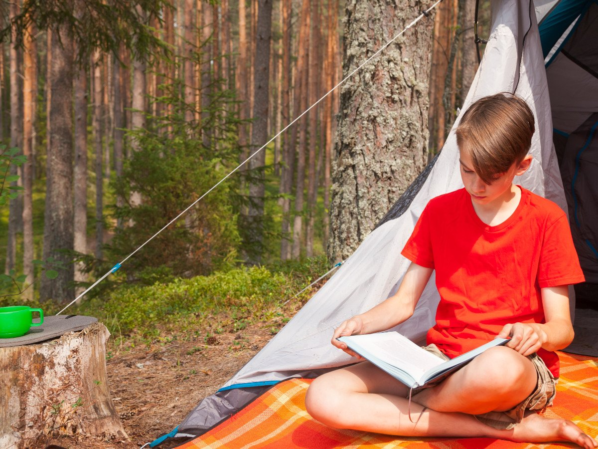 Boy reading in a tent