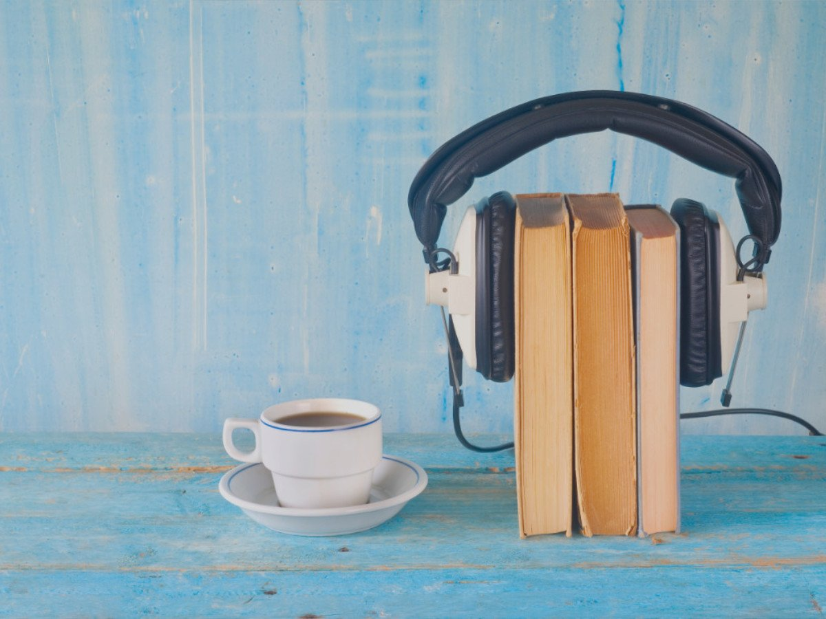 Headset on books beside a cup to tea