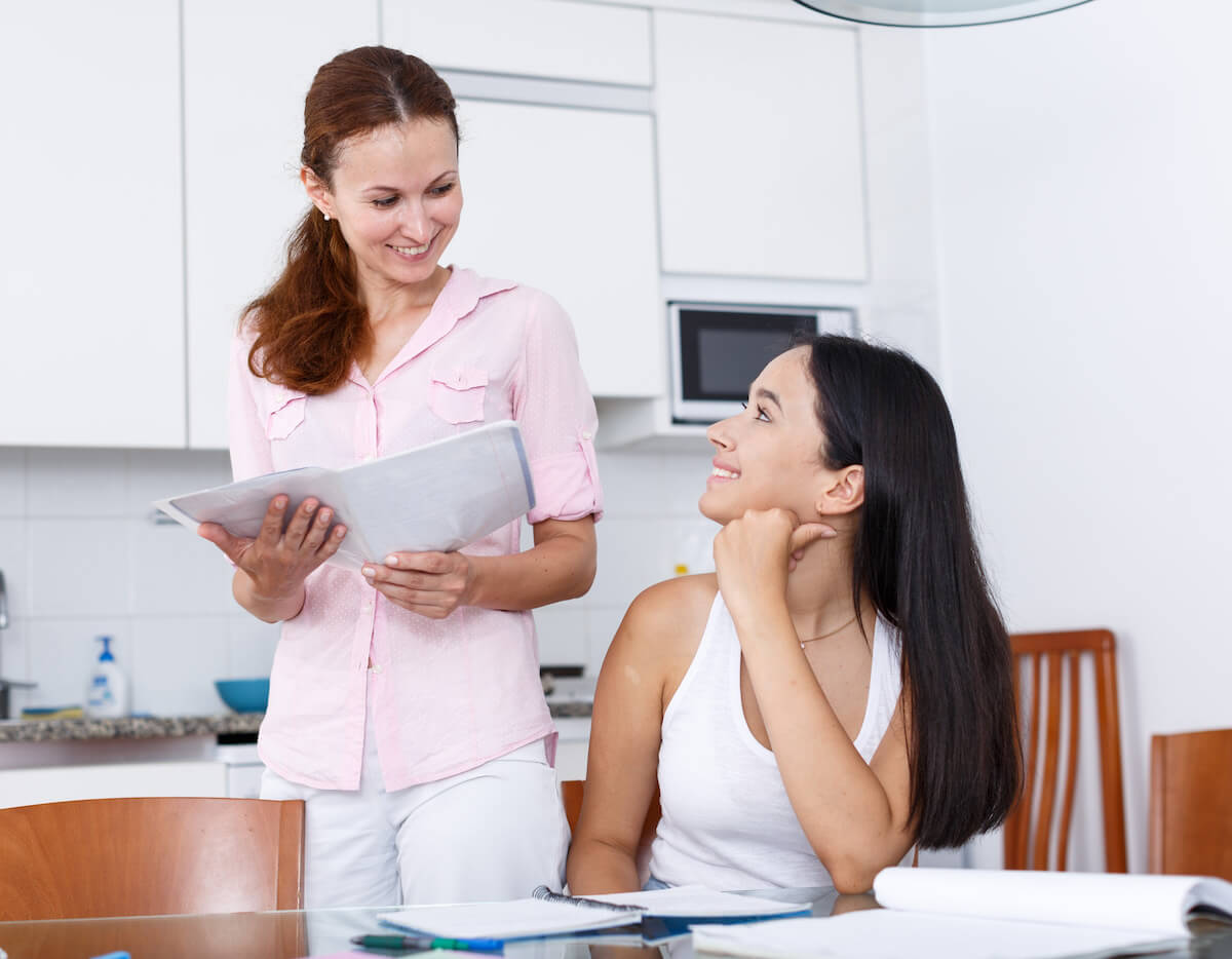 Mother smiling at daughter with work in hand