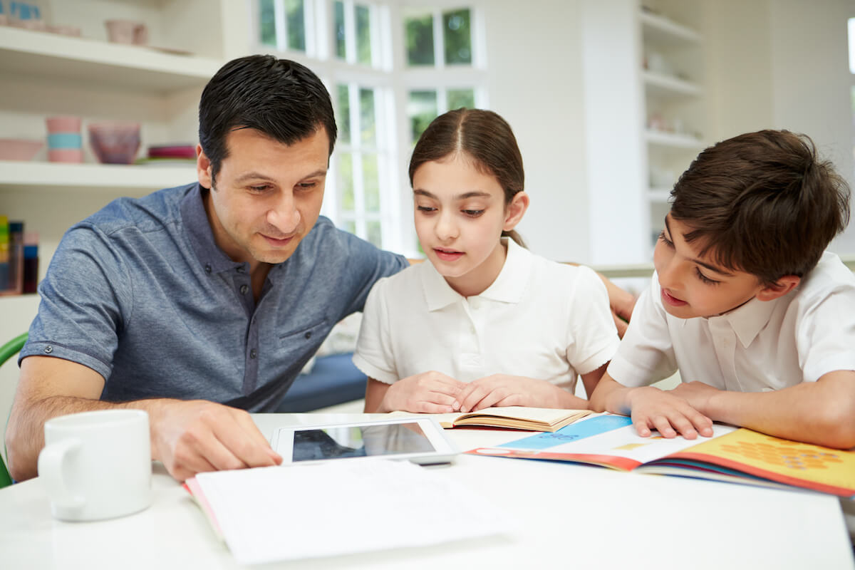 Father helping daughter and son with homework