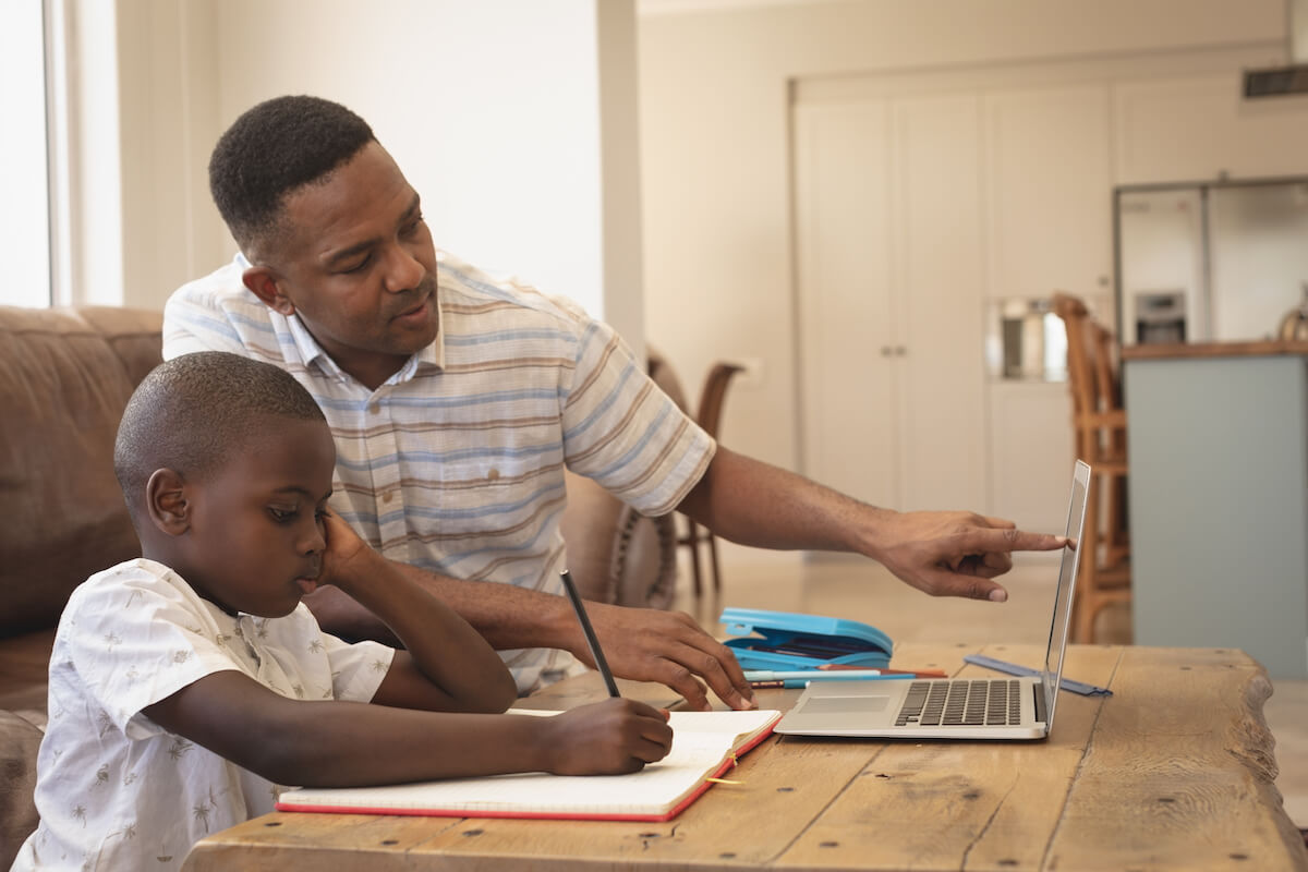 Father helping son with homework on laptop