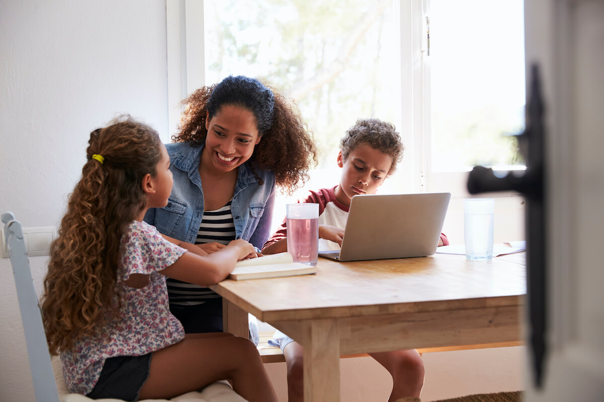 Mother helping daughter and son with homework