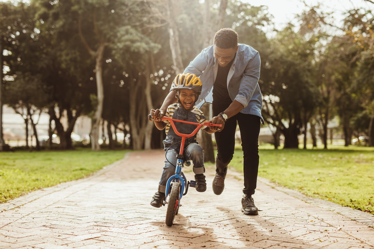 Dad having fun with son learning how to ride a bike