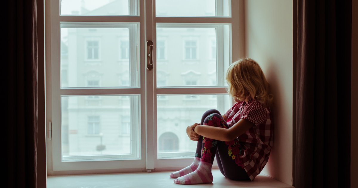 Child sitting alone at window sill looking out